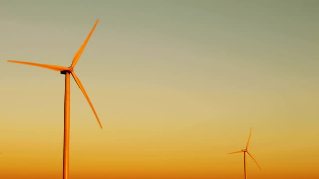 Wind turbines for alternative energy at sunset video