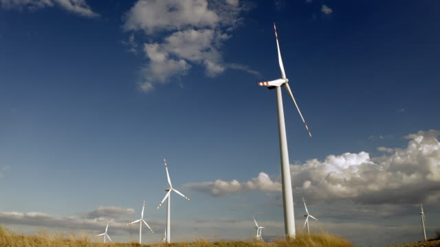 Wind Turbines In A Wind Farm For Energy Production Generating Clean Green And Environmentally Friendly Energy On Open Grass Field