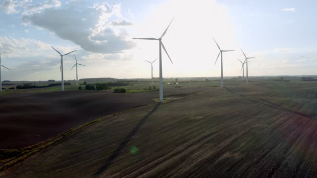 Wind Turbines In A Wind Farm For Energy Production Generating Environmentally Friendly Energy On Open Grass Field