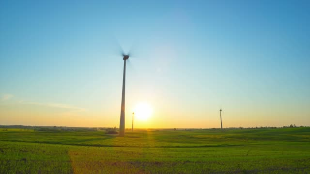 Wind turbines in the field and sunset, time-lapse video