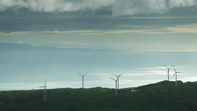 vídeos de stock e filmes b-roll de wind turbines silhouetted against shining sea - wellington