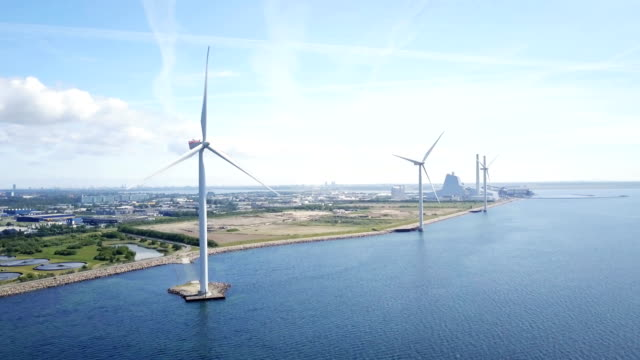 Wind turbines Aerial drone shot of of wind turbines in the ocean at Avedøre, Copenhagen, Denmark. The windmills in the foreground stand in contrast to the coal power plant in background. Blue sea and blue sky with warm lens flare. denmark stock videos & royalty-free footage