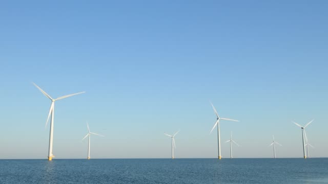 Wind turbines with turning blades in the wind in an offshore windpark
