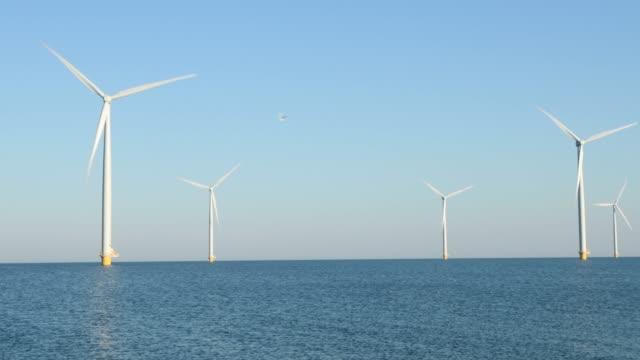 bir offshore windpark rüzgarda bıçaklar dönüm ile rüzgar türbinleri - kule stok videoları ve detay görüntü çekimi