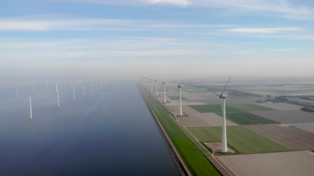 Windmill farm in the Netherlands, windmill turbine flowers and farmers working on the land, green energy in the Netherlands