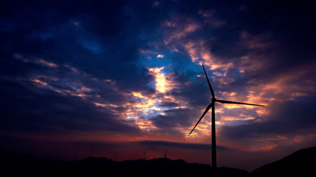 Windmills turbine sunglow at sunrise 4K UHD Scene of wind turbine and electrical towers at sunrise on rolling hills,South China.4K UHD Time Lapse Video propeller stock videos & royalty-free footage