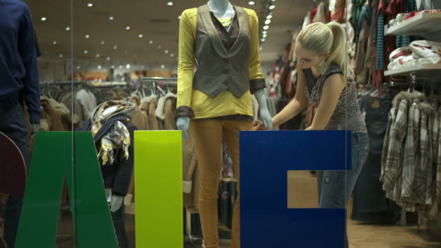 HD DOLLY: Window Dresser Adjusting Clothes On Mannequin HD1080p: DOLLY shot of a female window dresser arranging display for a clothing store,  adjusting clothes on a mannequin. saleswoman stock videos & royalty-free footage