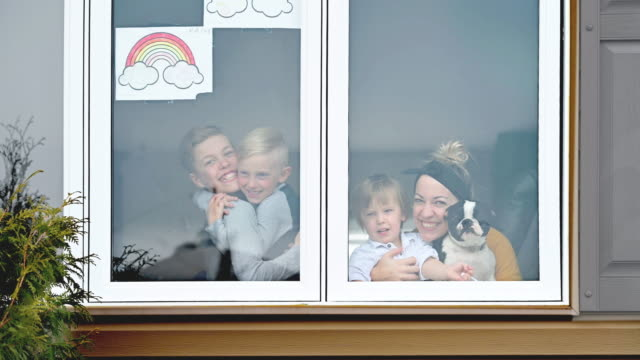 stockvideo's en b-roll-footage met het familieportret van het venster thuis met huisdierenhond en regenboogsymbool - buren