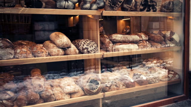 Fenêtre en boulangerie avec du pain frais en début de matinée, coup de pan. - Vidéo