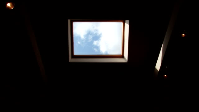 Window in the roof with view of running Сlouds video