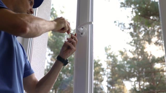 window service worker installazione maniglia su telaio in plastica - finestra video stock e b–roll