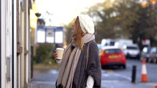 Window Shopping On Route A female walking down a street with takeaway hot drink in her hand glances at some shop windows and stops to take a longer look at one before moving on. sideways glance stock videos & royalty-free footage