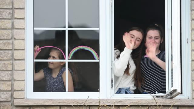 stockvideo's en b-roll-footage met het zustersportret van het venster thuis met huisdierenhond en regenboogsymbool - buren
