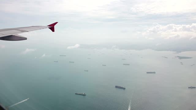 vídeos y material grabado en eventos de stock de vista de la ventana 4k desde el avión de muchos buques de carga en el puerto de singapur - anclado