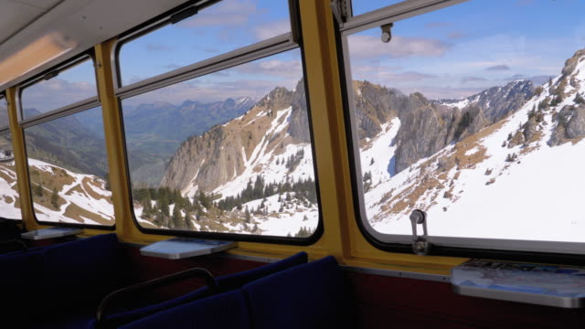 Window view of a Moving Mountain Train on the Snowy Switzerland Alps. Montreux City