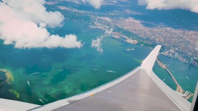 window view of an airplane over miami area with sea and cays - skrzydło samolotu filmów i materiałów b-roll