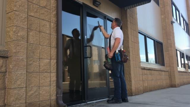 vidéos et rushes de lave-vitres nettoie les portes de construction - raclette