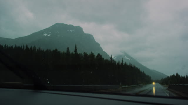 Windshield Wipers Clean Rain off of a Vehicle's Windshield while Driving along a Wet Highway in the Canadian Rocky Mountains Surrounded by Forests in Jasper National Park under an Overcast Sky at Twilight in Alberta, Canada