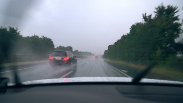 MS Windshield wipers clearing rain off car driving along freeway