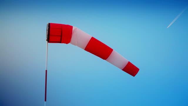 rękaw-wskaźnik wiatru na niebieskie niebo i samolot - rękaw filmów i materiałów b-roll