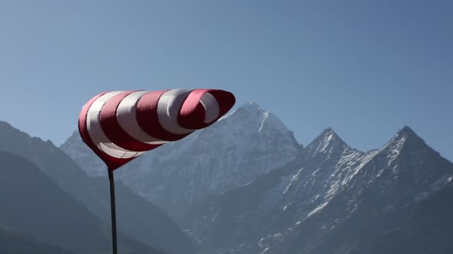 windsock blowing in wind with himalaya mountain peaks in background - rękaw filmów i materiałów b-roll