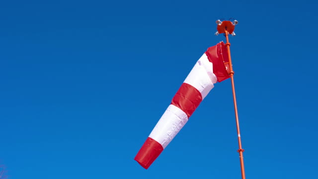 windsock develops on blue cloudless sky background. - manica video stock e b–roll