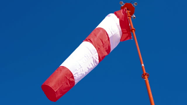 Windsock develops on blue cloudless sky background. Windsock with red and white stripes develops on blue cloudless sky background. Weathersock show direction of wind blowing and speed. Cone equipped floodlights on top surrounding it. sleeve stock videos & royalty-free footage