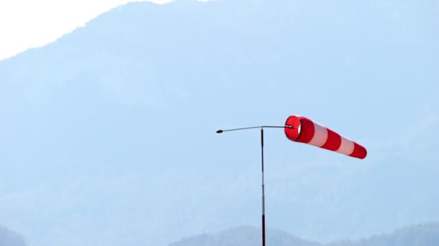 slo mo windsock showing the direction of wind in sunshine - rękaw filmów i materiałów b-roll
