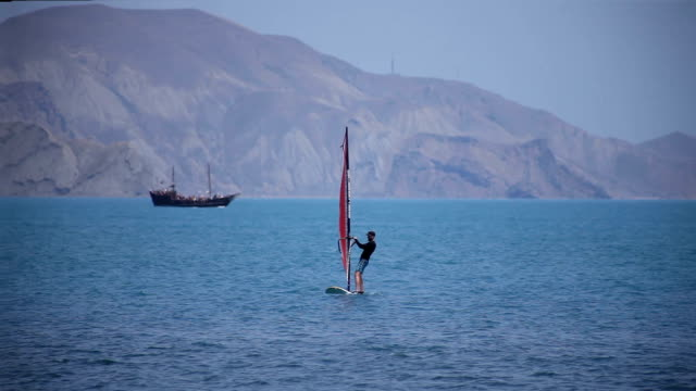 Windsurfers swim in the sea against the background of mountains video