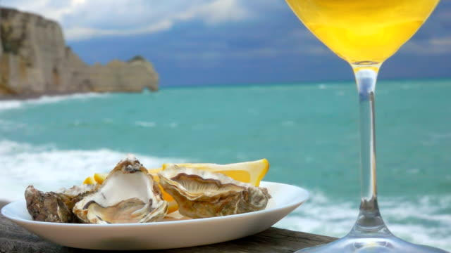 vídeos de stock e filmes b-roll de wine and a plate of oysters with lemon - cru