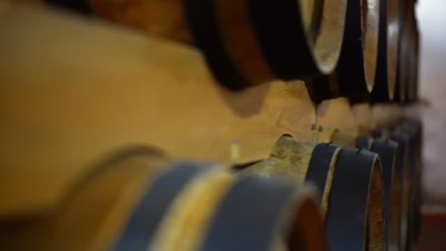 vídeos de stock e filmes b-roll de wine barrels stacked in a old cellar. oak barrel, aged wine italy - barrica
