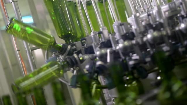 Wine bottle filling along a conveyor belt in a wine bottling factory video