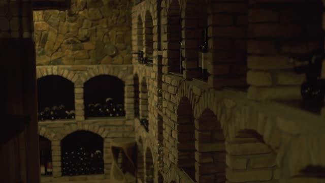酒瓶躺在棧在酒窖在酒館。在餐廳的石窖中貯存的葡萄酒玻璃瓶 - 石材 個影片檔及 b 捲影像