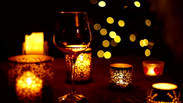 Wine falls into the glass on the background of flickering Christmas tree lights video