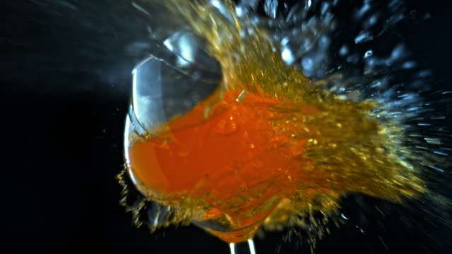 SLO MO LD Wine glass filled with orange liquid shattering