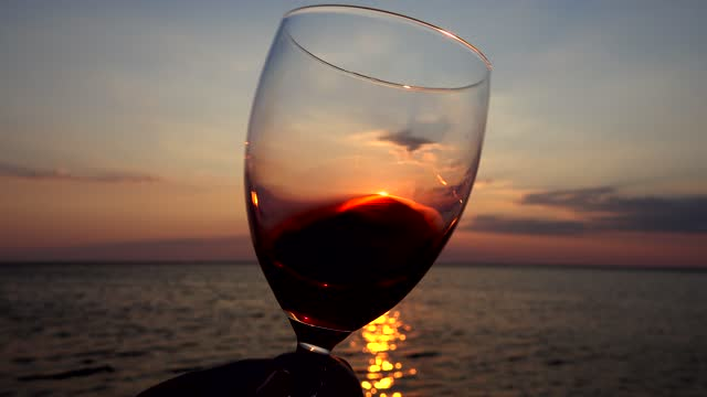 Wine in a glass against the background of the sunset over the sea. Slow motion. video