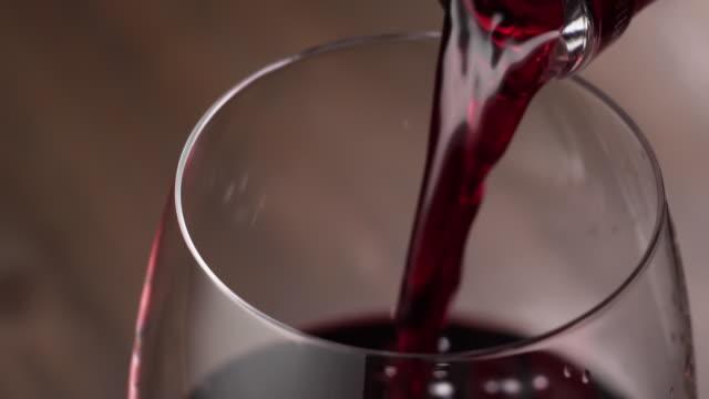 wein wird in ein glas gegossen, hochwinkelansicht, zeitlupe. - cabernet sauvignon traube stock-videos und b-roll-filmmaterial