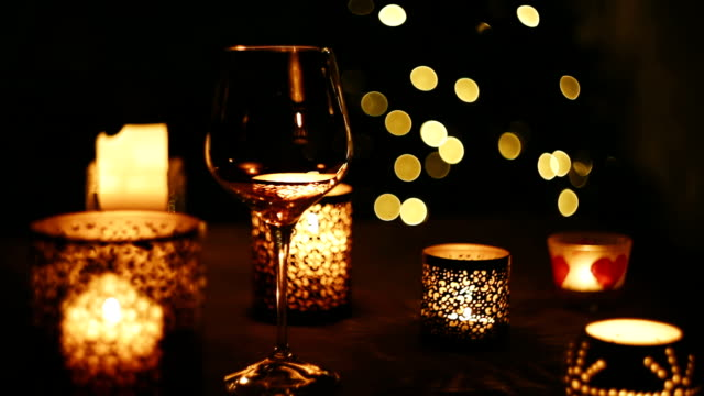 Wine is poured into a glass on the background of the flickering Christmas lights video