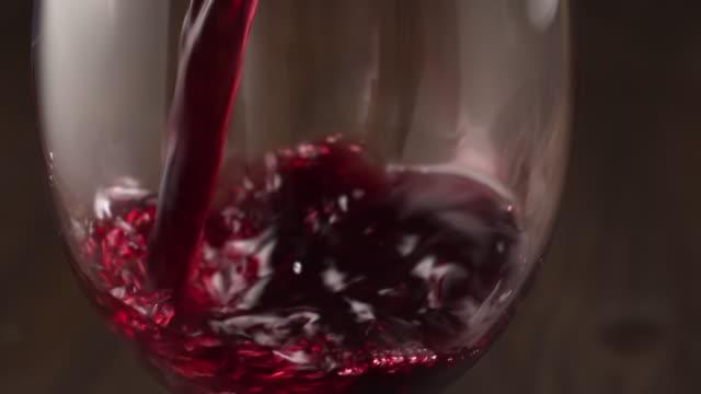 wein wird in ein glas gegossen, inzeitlupe. - cabernet sauvignon traube stock-videos und b-roll-filmmaterial