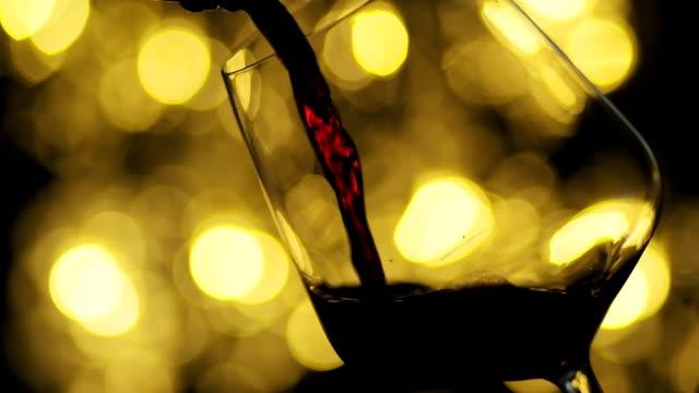 wein aus der flasche gießen. sommelier gießt einen ausgezeichneten rotwein in glas. - cabernet sauvignon traube stock-videos und b-roll-filmmaterial
