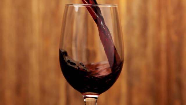 wein. rotwein gießt in weinglas auf holzhintergrund. makro-schuss - cabernet sauvignon traube stock-videos und b-roll-filmmaterial