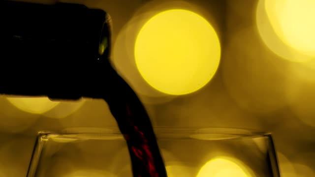 wein. rotwein gießt in weinglas über gelben girlanden hintergrund. - cabernet sauvignon traube stock-videos und b-roll-filmmaterial
