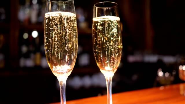 vidéos et rushes de verre à vin avec des boissons alcoolisées avec des bulles sur fond flou - flûte à champagne