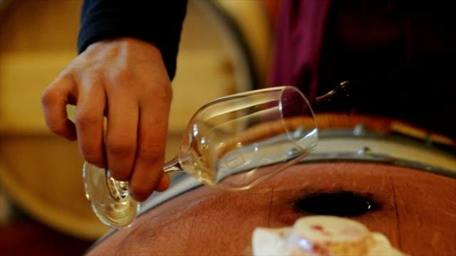 Winemaker in cellar making wine test. video