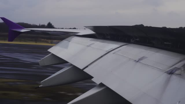 wing of airplane flying and landing flaps at the airport - battere le ali video stock e b–roll