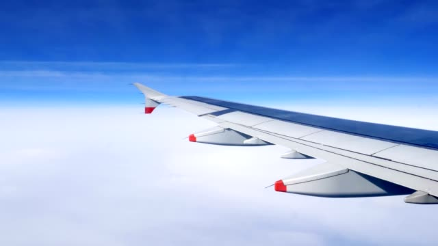 Wing of an airplane flying above the clouds video