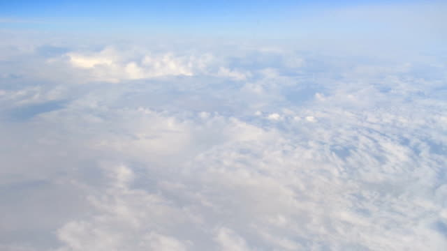 Wing of an airplane flying above the clouds with blue sky. video