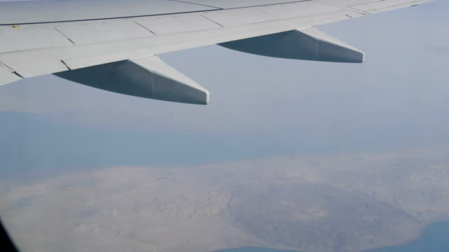 Wing of an airplane flying over the ground video