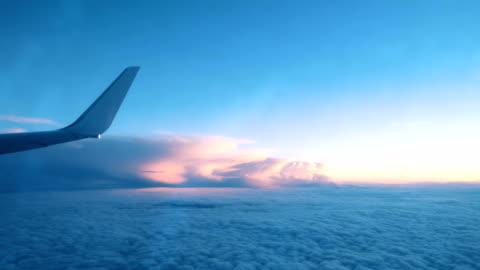 vidéos et rushes de aile d'un avion d'une fenêtre de voler au-dessus des nuages d'un avion au coucher du soleil - avion
