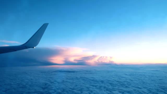 vingen på ett flygplan från ett fönster som flyger över molnen i ett flygplan vid solnedgången - airplane bildbanksvideor och videomaterial från bakom kulisserna
